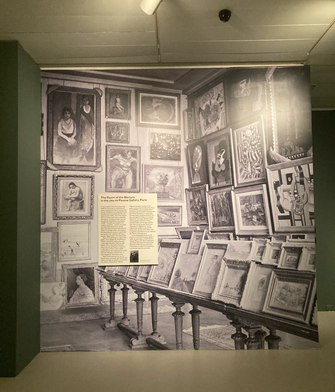 """The entry to the exhibit features a photo of the """"Room of the Martyrs"""" at the Jeu de Paume gallery where the Nazis hung much of their looted art before deciding its fate. The Room of the Martyrs was filled with art considered degenerate and often slated for destruction. by the Forward"""