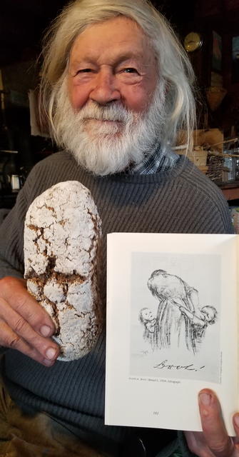 "Bread and Kollwitz: Bread & Puppet founder Peter Schumann holds a loaf of bread and a picture of Kollwitz's ""Brot"" poster"