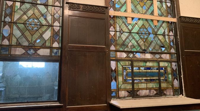 The stained glass windows depicting Jewish iconography have survived decades longer than the congregation itself in the B'nei Bezalel building.  from the front