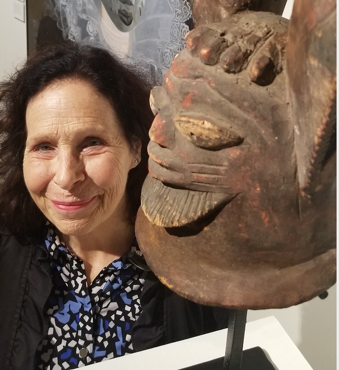 Biographer of Kollwitz: Martha Kearns, seen here with a mask at an exhibit of artwork by contemporary Nigerian painter Wole Lagunju, is the author of Kathe Kollwitz: Woman and Artist