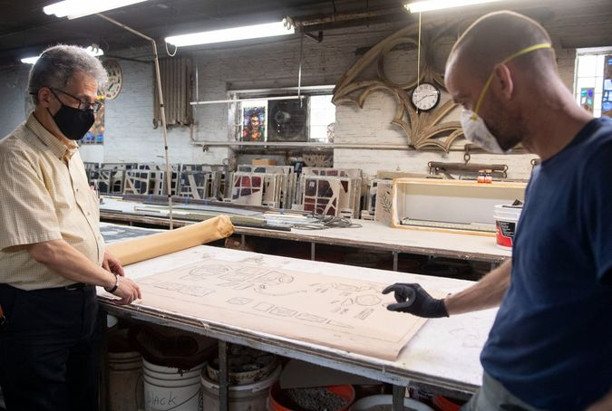 David Parrendo, left, Business Director at Hunt Stained Glass Studios Inc, and Bryan Nightingale, Master Glazier, talk about the work they do on the Tree of Life stained glass windows at Hunt Stained Glass Studios Inc on the South Side.  from the front