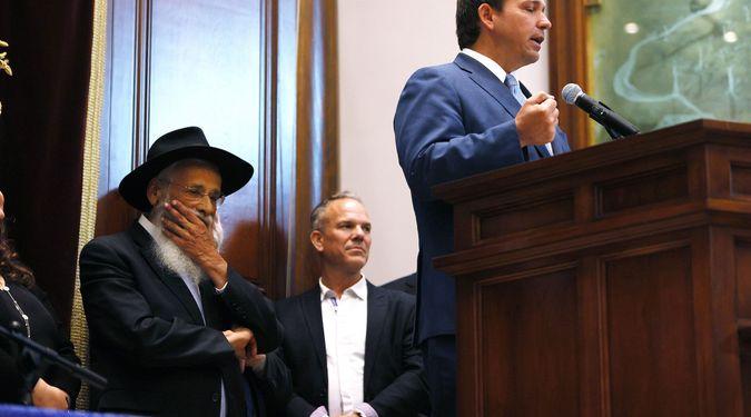 Rabbi Sholom Lipskar listens as Florida Gov. Ron DeSantis speaks during a press conference at the Shul of Bal Harbour on June 14, 2021 in Surfside, Florida. by the Forward